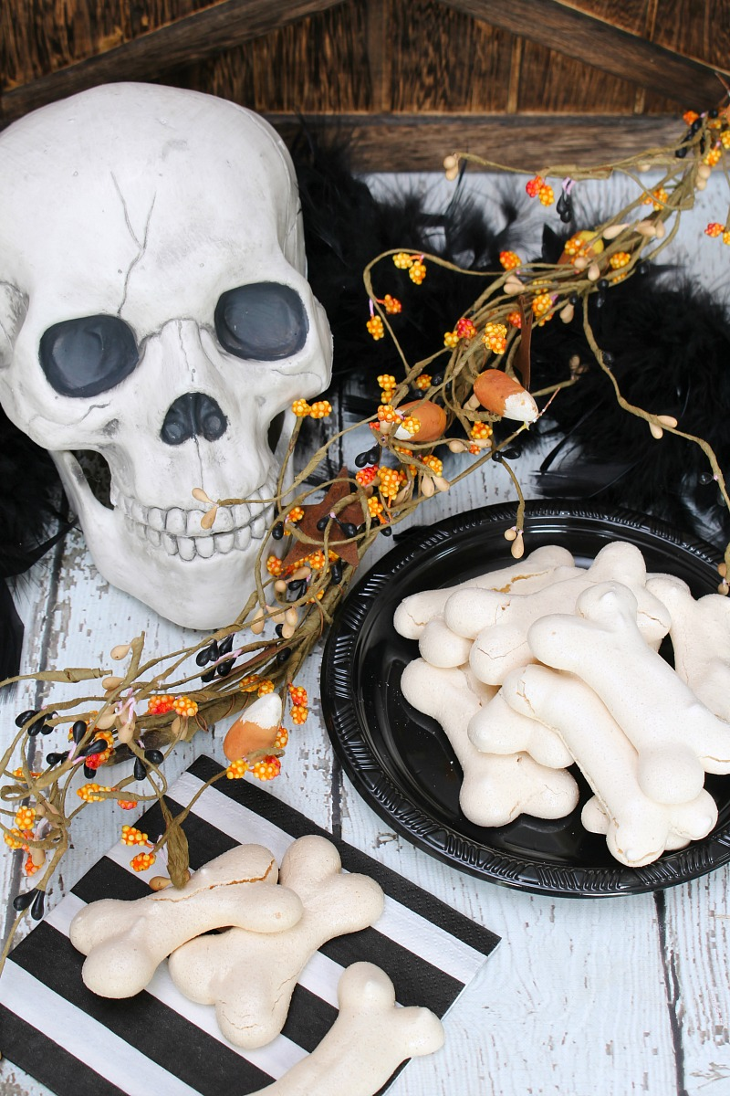 Meringue bones Halloween treats on a black plate with skull.